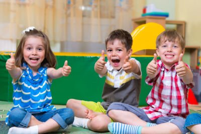 three preschoolers giving thumbs up